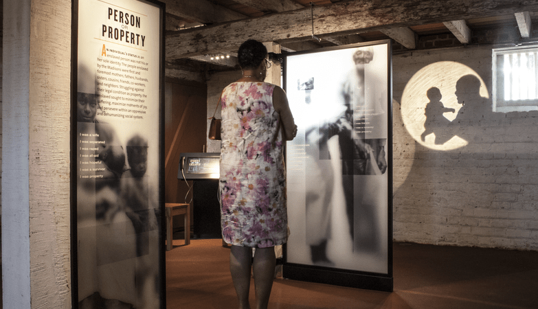 Woman looking at an exhibit describing the history of slavery.