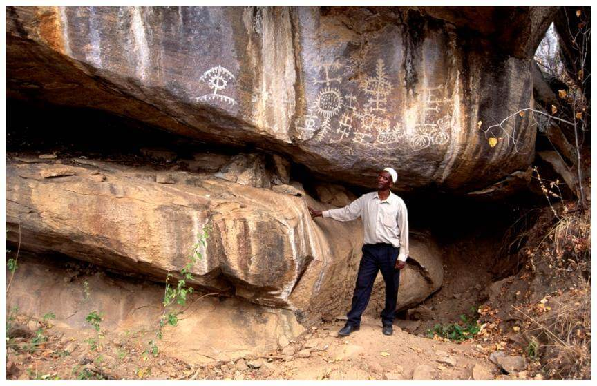 Overhanging boulders displaying ancient rock art with protected area