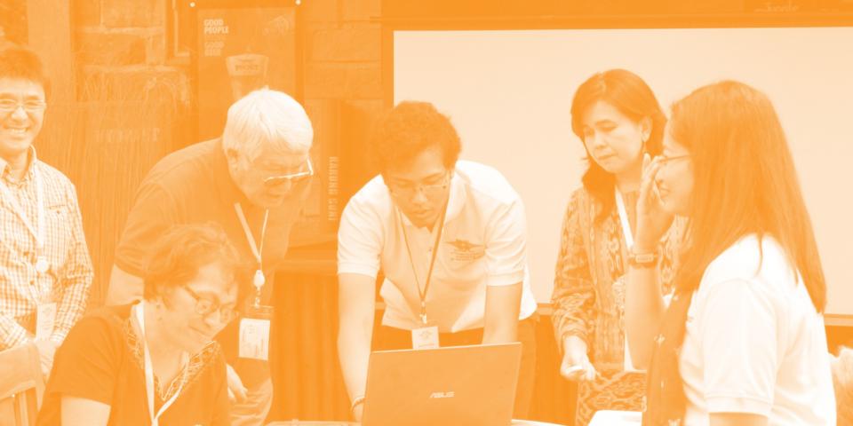 INTO Online Delegates gather around digital presentation